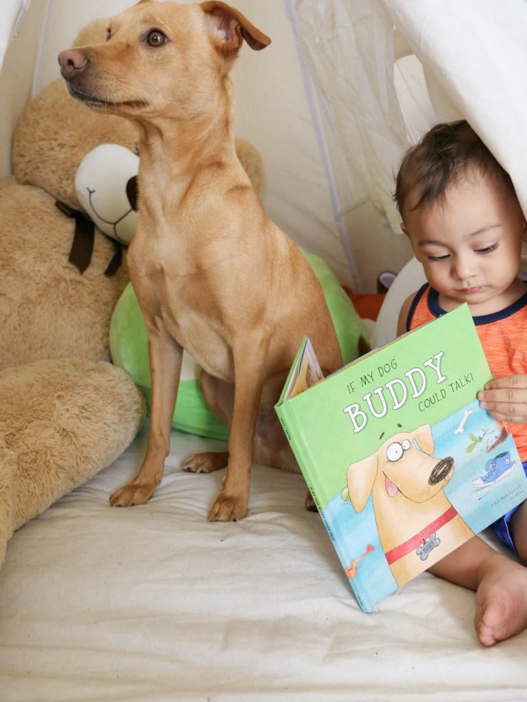 baby sitting down reading book next to dog