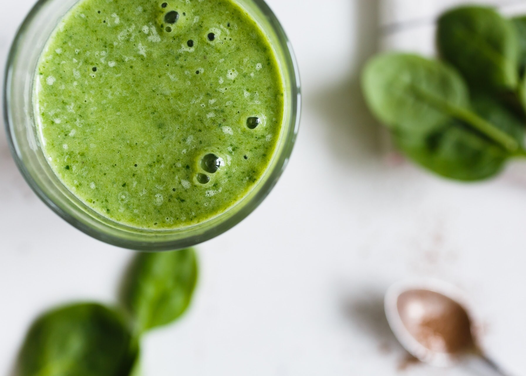 Green smoothie with brass spoon