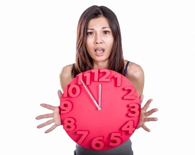 Asian woman holding clock