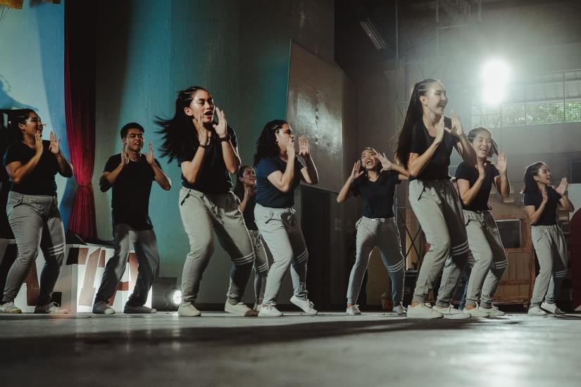 A group of teens dance in a studio class.