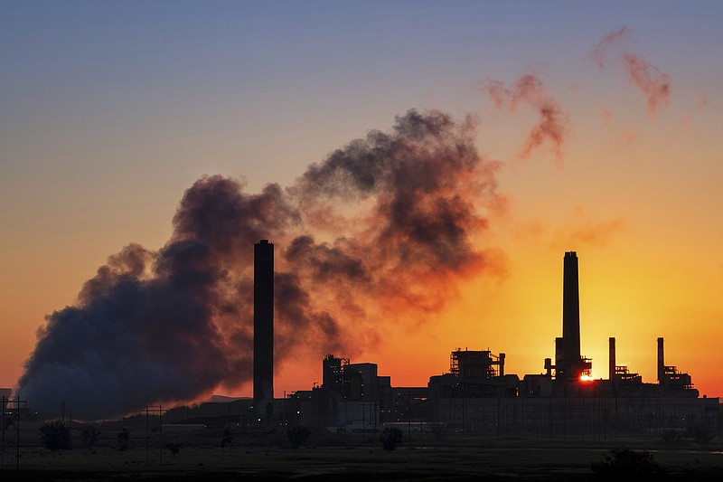 The Dave Johnson coal-fired power plant is silhouetted against the morning su...