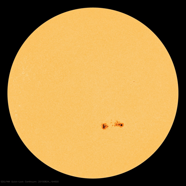 A big yellow ball- the sun - with two small sunspot groups in red.