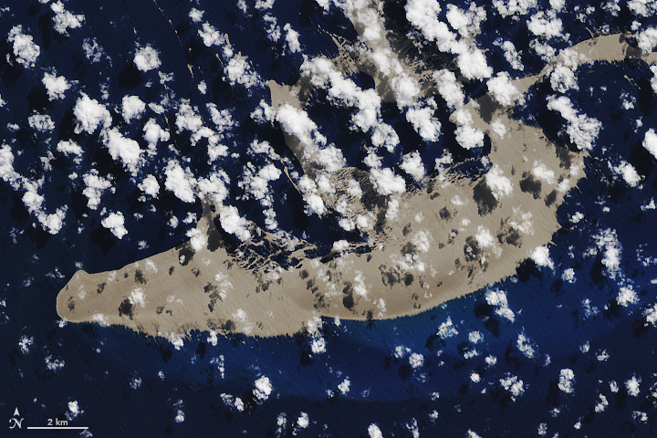 Aarial view, blue sea, scattered white clouds, tan raft nearly filling image.
