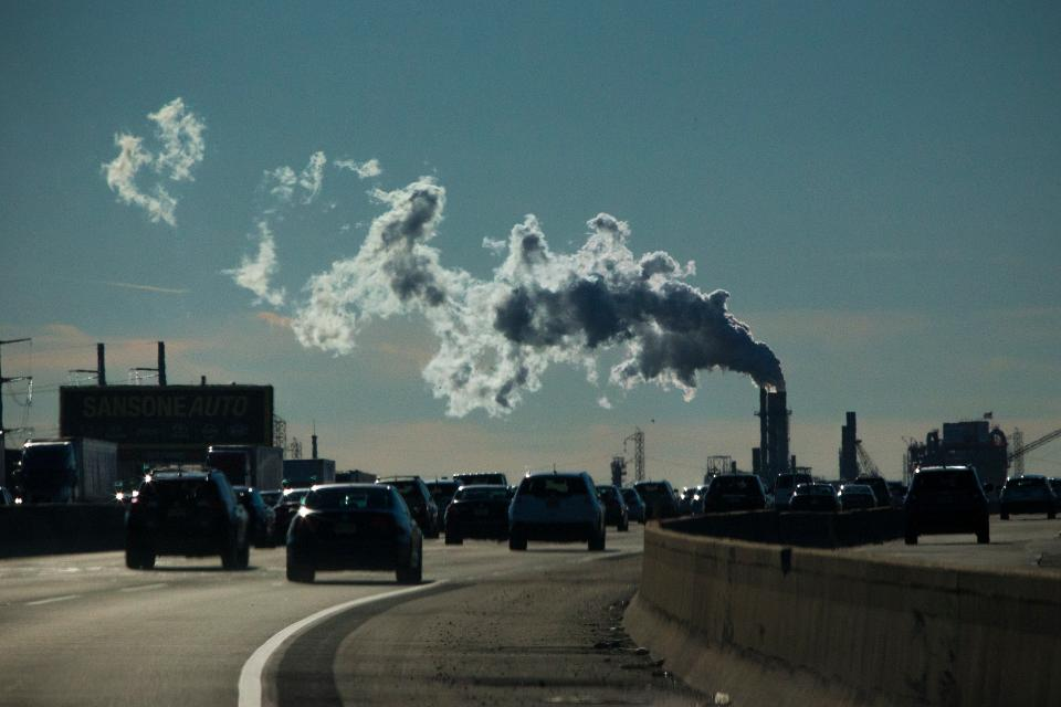 Vehicles move along the the New Jersey Turnpike while a factory emits smoke in 2017.