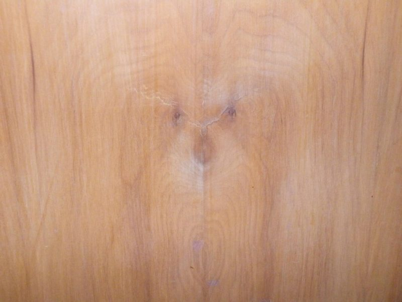 Symmetrical grains of wood with spots for nose and two eyes.