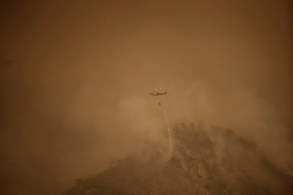 Helicopters dropping water above Santa Anita Canyon in Arcadia, Calif., while battling the Bobcat Fire on Sunday.