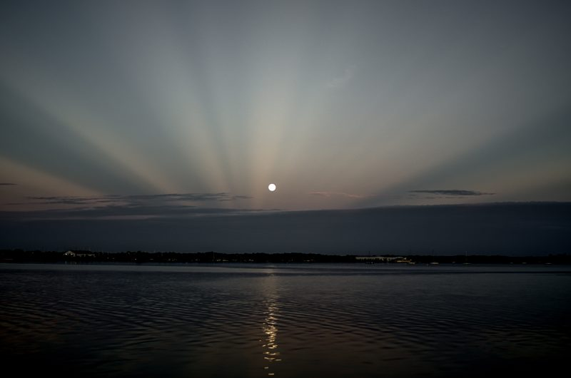 Pinky-gray rays converging on horizon with round bright full moon right in the center, all reflected in body of water.