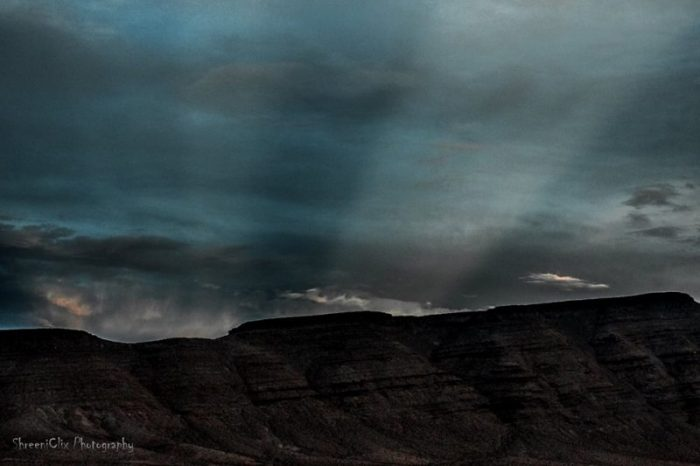 Wide light rays through sinister dark clouds over a mountain landscape.
