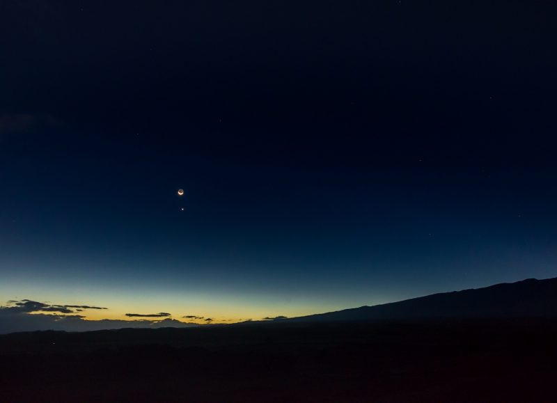 Small, bright moon above single star-like object, the planet Venus, in early dawn sky.