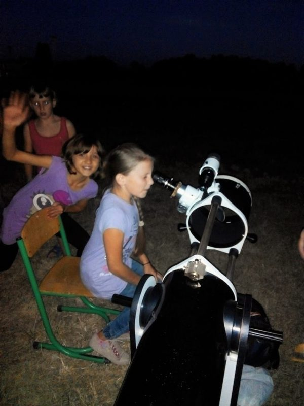 A sitting child looking in the eyepiece of a large amateur telescope, other kids waiting.