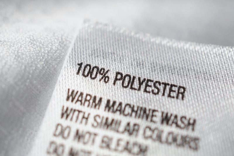 Closeup of a label from a garment saying '100% polyester' with washing instructions.