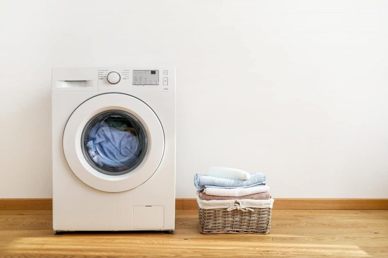 A front-loader washing machine with a basket of folded fabric items next to it.