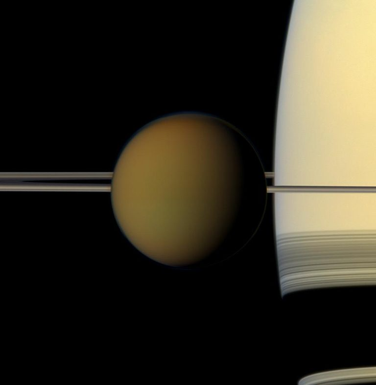 Hazy brownish ball with Saturn's thin rings on edge behind, and part of Saturn.
