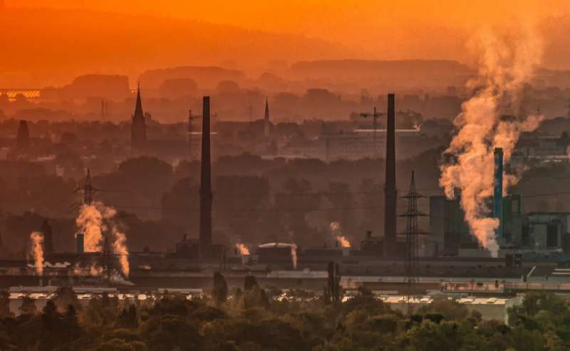 Orange-lit scene of industrial landscape with smokestacks and dirty air.