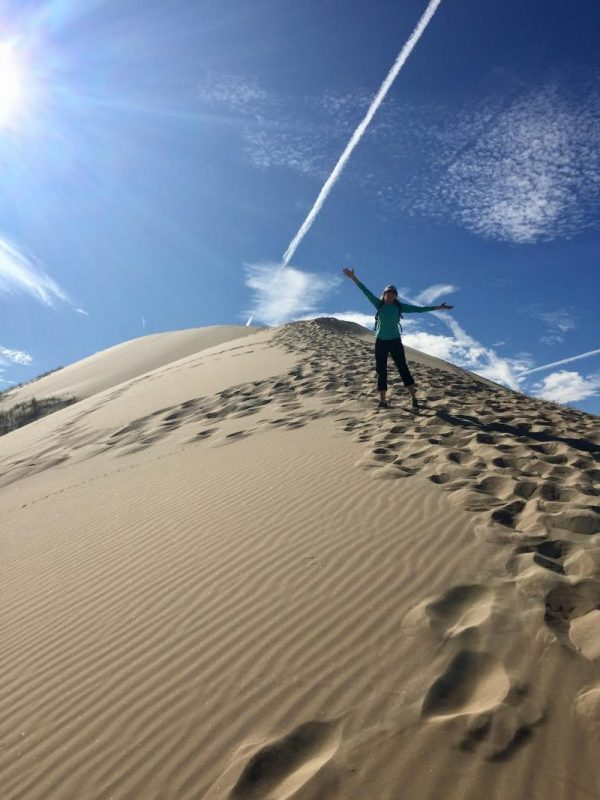 Top of sand dune with person stretching up arms and diagonal jet contrail with a shadow above.
