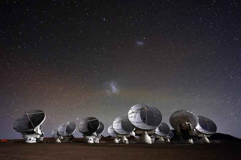 Dish-type antennas staring at a star-strewn sky.