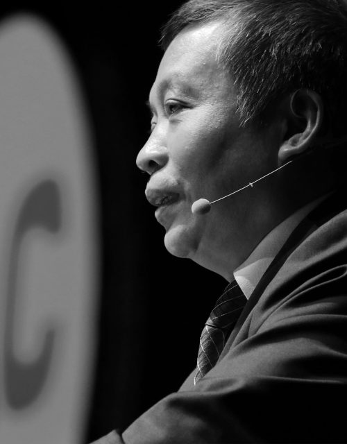 Profile of an Asian man speaking into a microphone.