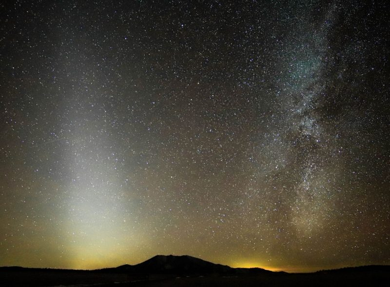 Long fuzzy patch of light with irregular band of Milky Way and other stars in the background sky.
