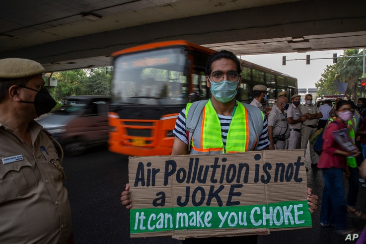 A student activist holds a placard as he participates in a protest march against climate change in New Delhi, India, Friday,…
