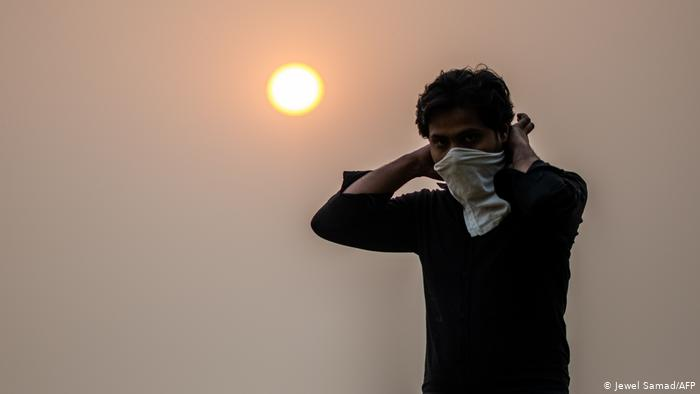 A man surrounded by smog wears a scarf around his face.