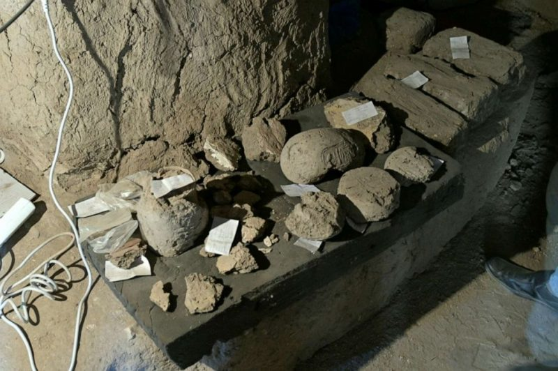 Artifacts with labels laid on stone shelf at archaelogical site.