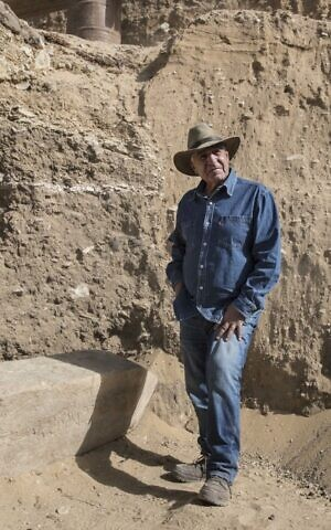 A middle aged man in work clothes and a hat, in front of an archeological dig site.