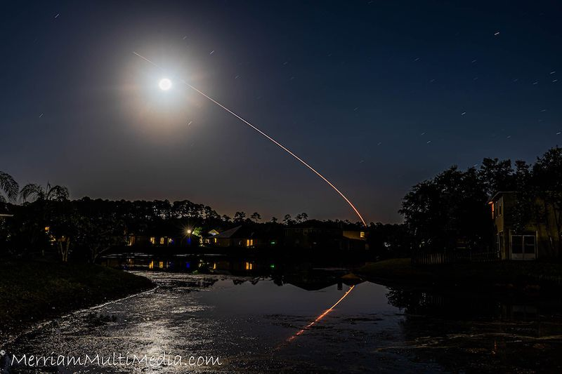 Bright light with aura, with a path of rocket seemingly heading towards it. Water in the foreground with the scene reflected.