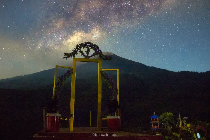 Cloud of stars behind mountain, manmade arch in foreground.