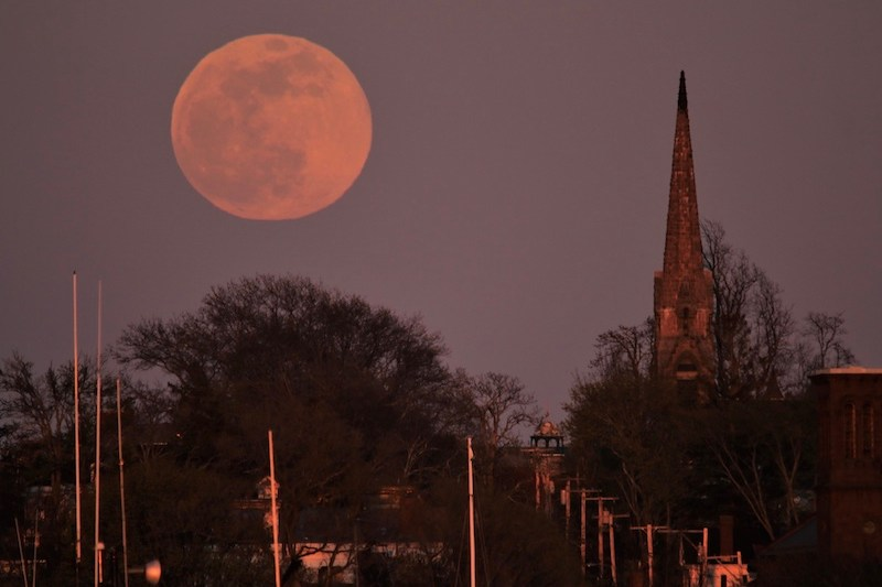 Pink large full moon next to a church tower.