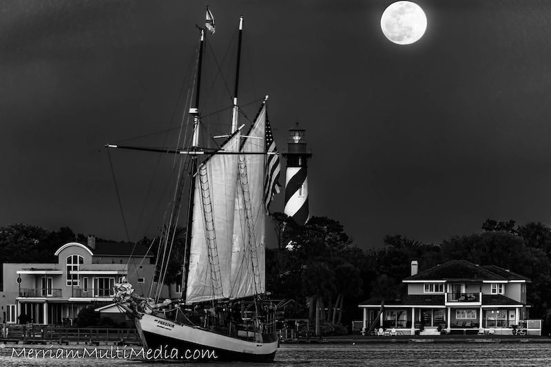 Greyscale of sailboat, lighthouse and a full moon at top right.