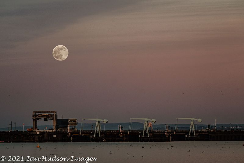 full moon on wispy pink sky above drawbridges, with water in the foreground.