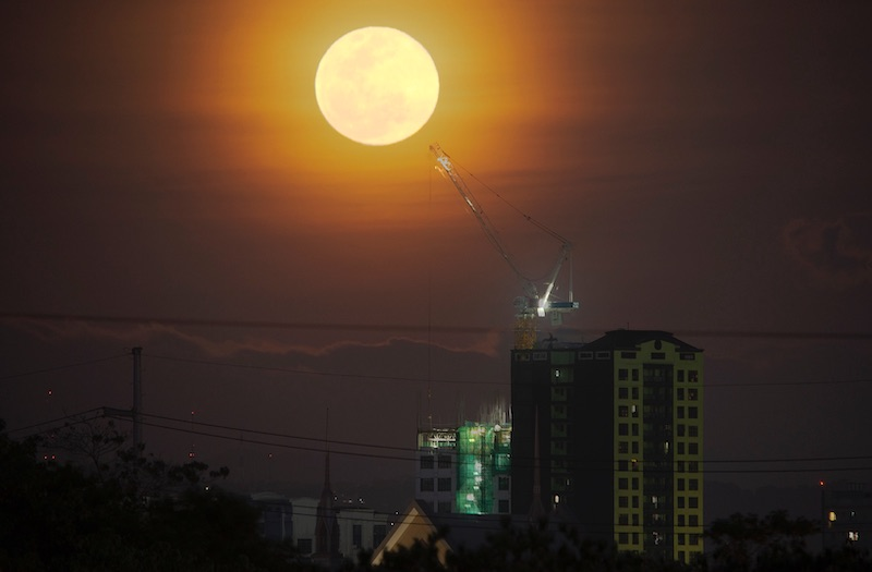 Bright shining moon with orange halo over city-scape.