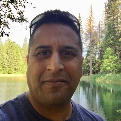 Headshot of man in front of lake and trees.