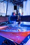 A water jet machine utilizes high pressure water and sand to cut 2D profiles out of flat sheets of material.