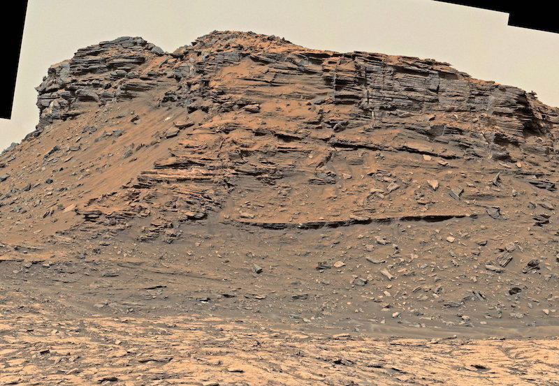 Bare rocky outcrop with horizontal layers.