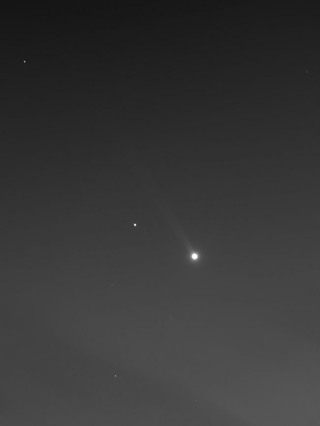Dot of light with long, fuzzy, pale tail streaming to upper left.