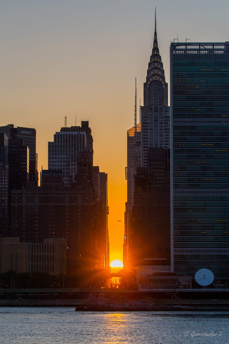 Manhattanhenge is tall buildings each side of golden sunset, half the sun above the horizon, waterway in foreground.