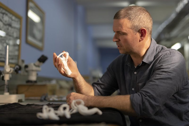 Man holding and examining a fossil bone.