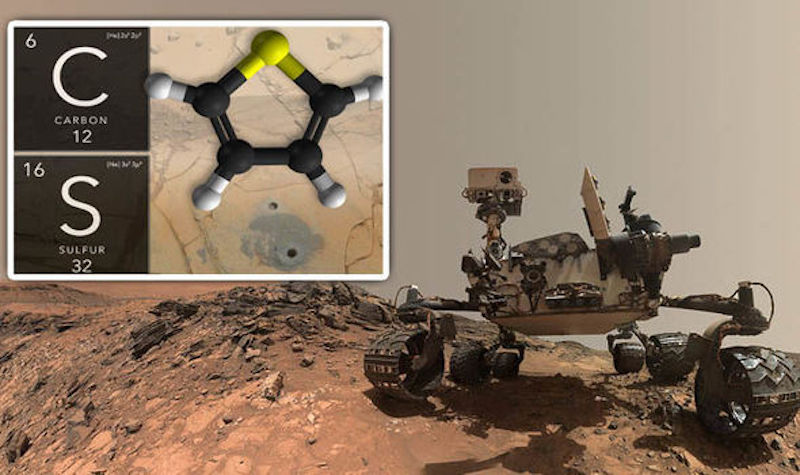 Robotic rover on brownish rocky terrain with inset image of a molecule.