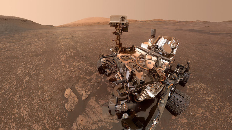 Robotic rover on brownish rocky terrain with hills in background.