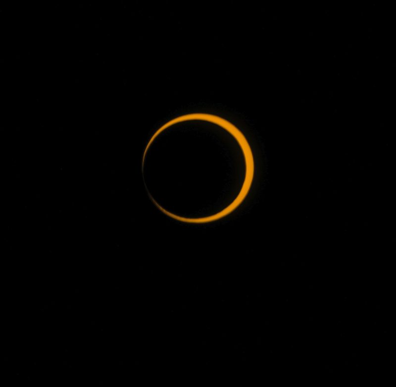 Black sky and nearly complete circle of orange with black center.