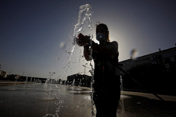 A woman wearing a protective face mask splashes her hands in a jet of water