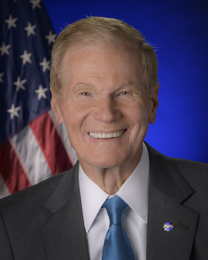 Smiling man in suit and tie with American flag behind him.