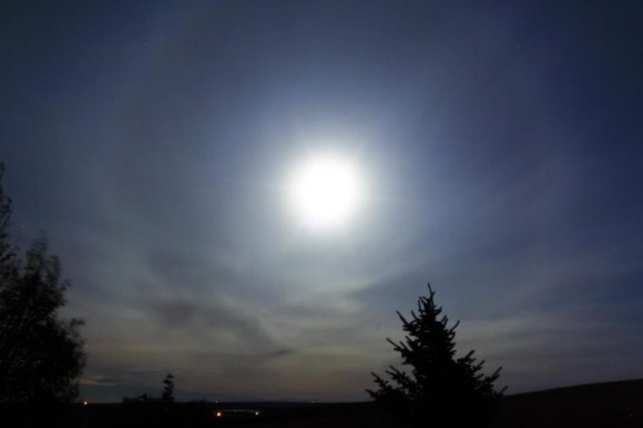 Faint halo around the bright moon among wispy clouds.