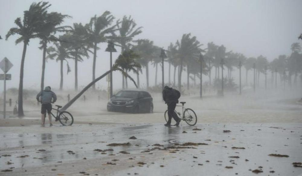 Two people walk their bicycles along a flooded street on the waterfront of Fort Lauderdale, Fla., as Hurricane Irma passes through on September 10, 2017. Photo: THE CANADIAN PRESS
