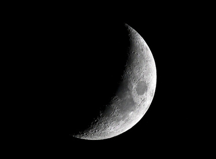 Crescent moon with many mountains, seas, and craters visible.