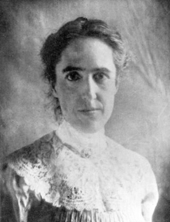 Woman in 1910 costume with her hair up.
