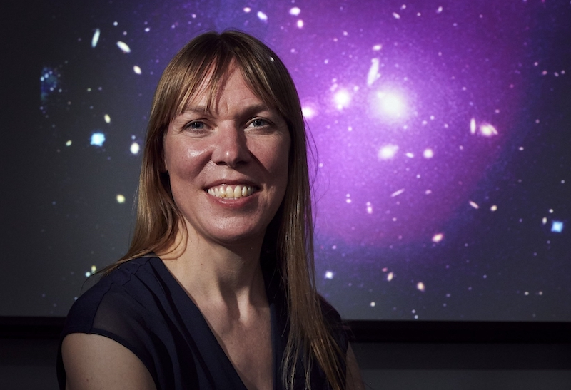 A white woman smiles in front of a purple backdrop with white dots, or stars.