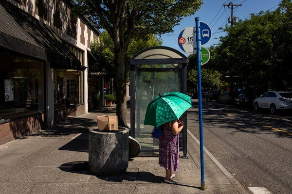 A bus rider carried an umbrella to protect herself from the sun during a deadly heat wave in Portland, Ore., last month.