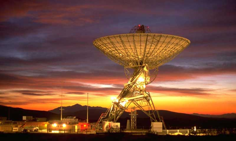 Tall dish-shaped radio telescope all lit up against a gorgeous yellow and red sunset.